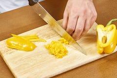 Nahaufnahme auf den Händen, die gelben Pfeffer auf Berufsküche schneiden Lizenzfreies Stockbild