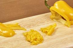 Nahaufnahme auf den Händen, die gelben Pfeffer auf Berufsküche schneiden Stockbild