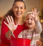 Nahaufnahme auf den Mutter- und Babyhänden geschmiert im Mehl Lizenzfreies Stockbild