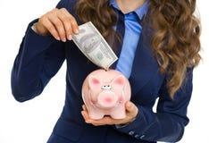 Nahaufnahme auf der Frau, die 100 Dollar Banknote in Sparschwein setzt Lizenzfreies Stockfoto