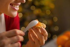 Nahaufnahme auf der Frau, die Orangenmarmelade auf Plätzchen setzt lizenzfreie stockfotos