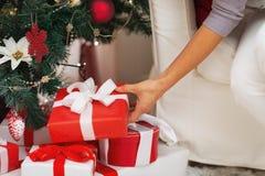 Nahaufnahme auf der Frau, die Präsentkarton unter Weihnachtsbaum setzt Stockfotografie