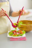 Nahaufnahme auf der Frau, die Salat in Platte setzt Lizenzfreies Stockfoto