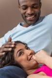 Nahaufnahme auf der glücklichen Afroamerikanerfrau, die auf Mannbeinen liegt Stockbild