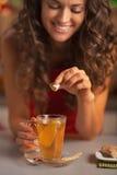 Nahaufnahme auf der glücklichen Frau, die brauner Zuckerwürfel in Ingwertee setzt stockfotografie