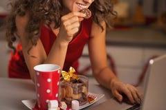 Nahaufnahme auf der glücklichen Frau, die Weihnachtssnäcke und usign Laptop hat lizenzfreie stockfotografie