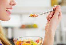 Nahaufnahme auf der glücklichen jungen Frau, die Fruchtsalat isst Stockfotos