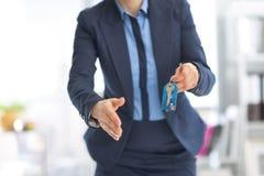 Nahaufnahme auf der glücklichen Geschäftsfrau, die Schlüssel gibt Stockbild