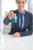 Nahaufnahme auf der glücklichen Geschäftsfrau, die Schlüssel gibt Stockfotografie