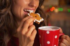 Nahaufnahme auf der jungen Frau, die Weihnachtsplätzchen isst Lizenzfreie Stockfotos