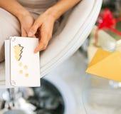 Nahaufnahme auf der jungen Frau, die Weihnachtspostkarte hält Stockbilder