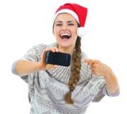 Nahaufnahme auf der jungen Frau im Weihnachtshut zeigend am Handy lizenzfreie stockfotografie
