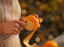 Nahaufnahme auf der jungen Hausfrau, die orange Schale entfernt Stockbilder