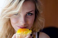 Nahaufnahme auf der schönen jungen blonden Frau, die den köstlichen Kuchen lächelt schmeckt, Kamera portrat betrachtend Lizenzfreie Stockfotografie