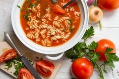 Nahaufnahme auf der Tomatensuppe gemacht vom Knoblauch und vom Basilikum Lizenzfreie Stockfotos
