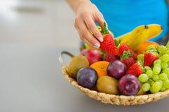 Nahaufnahme auf der weiblichen Hand, die Erdbeere von der Platte von Früchten nimmt lizenzfreie stockfotos