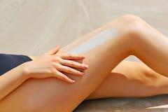 Nahaufnahme auf der weiblichen Hand, die Sonnenschutzcreme auf Bein anwendet Stockfoto