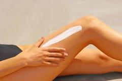 Nahaufnahme auf der weiblichen Hand, die Sonnenschutzcreme auf Bein anwendet Lizenzfreie Stockfotos
