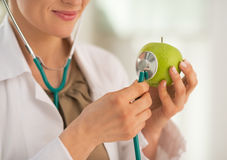 Nahaufnahme auf Doktor, der Stethoskop auf Apfel verwendet Lizenzfreies Stockbild