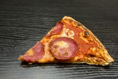 Nahaufnahme auf einem Stück Pizza auf einem dunklen hölzernen Hintergrund Lizenzfreies Stockfoto