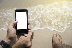 Nahaufnahme auf einer Mannhand, die intelligentes Telefon auf dem Strand hält Legen am Strand äußerer Hintergrund Sonniger Tag Se Lizenzfreie Stockbilder