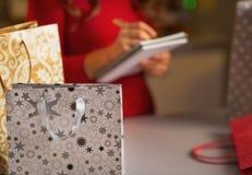 Nahaufnahme auf Einkaufstasche- und Frauenprüfungsliste von Geschenken stockbild