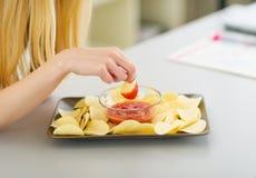 Nahaufnahme auf eintauchenden Chips der Jugendlichen in der Soße Lizenzfreie Stockbilder