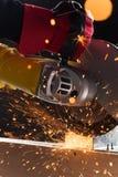 Nahaufnahme auf elektrischer Säge und Händen der Arbeitskraft Stockfotografie