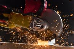 Nahaufnahme auf elektrischer Säge und Händen der Arbeitskraft mit Funken Stockbild
