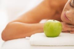 Nahaufnahme auf entspannter junger Frau auf Massagetabelle mit Apfel Lizenzfreie Stockfotografie