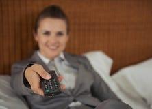 Nahaufnahme auf Fernsehfernbedienung in der Hand der Geschäftsfrau Lizenzfreie Stockfotografie