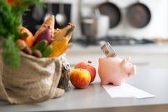 Nahaufnahme auf Geld im Sparschwein und in den Käufen stockfotografie