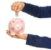 Nahaufnahme auf Geschäftsfrau übergibt das Setzen der Münze in Sparschwein Stockbilder