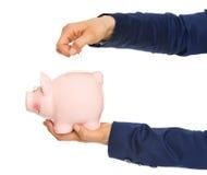 Nahaufnahme auf Geschäftsfrau übergibt das Setzen der Münze in Sparschwein Stockfoto
