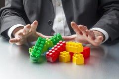 Nahaufnahme auf Geschäftsmann übergibt das Spielen mit Plastikziegelsteinen für Konzept des Bauvorhabens Stockbild