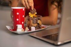 Nahaufnahme auf Hausfrau mit Snäcken unter Verwendung des Laptops Lizenzfreie Stockfotografie