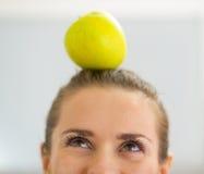 Nahaufnahme auf junger Frau mit Apfel auf Kopf Lizenzfreie Stockfotos