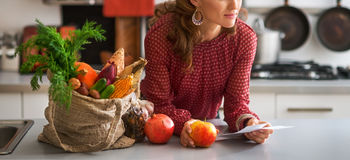 Nahaufnahme auf junger Hausfrau mit Kontrollen nach Einkauf lizenzfreies stockfoto
