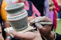 Nahaufnahme auf Künstler übergibt die Personifizierung eines Lehmkrugs, indem sie den Namen einer Person schreibt. Stockfotografie