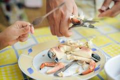 Nahaufnahme auf Krabbe und Händen mit Hintergrund der Geräte auf dem Tisch Exotischer Teller Lizenzfreie Stockfotos