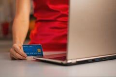 Nahaufnahme auf Kreditkarte in der Hand der Frau, die on-line-Käufe abschließt Stockfoto
