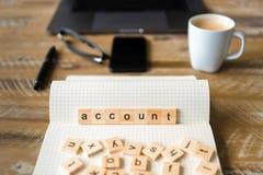 Nahaufnahme auf Notizbuch über hölzernem Tabellenhintergrund, Fokus auf Holzklötzen mit den Buchstaben, die Kontowort machen Stockfotografie
