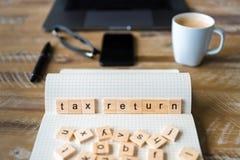 Nahaufnahme auf Notizbuch über hölzernem Tabellenhintergrund, Fokus auf Holzklötzen mit den Buchstaben, die Steuererklärungswörte Stockfoto