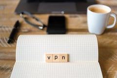 Nahaufnahme auf Notizbuch über hölzernem Tabellenhintergrund, Fokus auf Holzklötzen mit den Buchstaben, die VPN-Wort machen Lizenzfreie Stockfotos