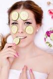 Nahaufnahme auf schöner blonder junger Dame, die den Spaß anwendet Scheiben der Gurke an ihrer Gesichtshaut u. an glücklichen Läc Stockbilder