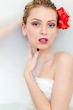 Nahaufnahme auf schöner blonder junger Frau mit blauen Augen und roten den Lippen, die im Whirlpool mit Milch liegen und Kamera b Stockfotografie