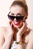 Nahaufnahme auf schöner blonder Pinupfrau mit Kamera der Sonnenbrille glückliches Lächeln u. Betrachten auf weißem Hintergrundport Stockfotos