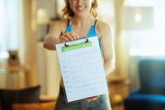 Nahaufnahme auf Sportfrau im modernen Wohnzimmervertretungs-Mahlzeitplan lizenzfreie stockfotos