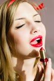 Nahaufnahme auf verlockender attraktiver sexueller junger blonder Pinupfrau zeichnet roten Lippenstift, den offene Lippen sinnlic Lizenzfreies Stockfoto