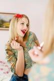 Nahaufnahme auf verlockender junger blonder Pinupfrau zeichnet in die roten Lippenstiftlippen des Spiegels Stockbild